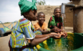 Three African children enjoying fresh, clean water JPEG